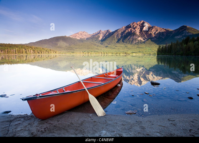 Red canoe at dawn on Pyramid Lake, Jasper National Park, Alberta, Canada. - Stock Image