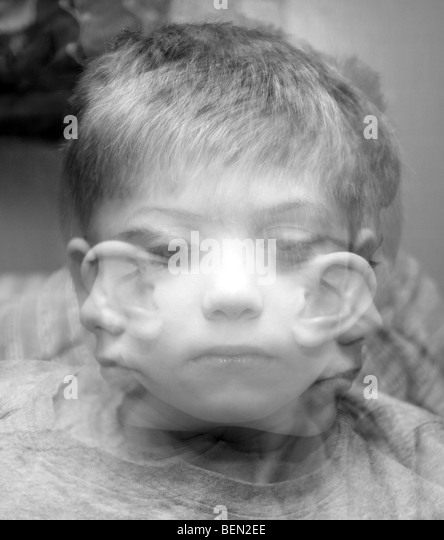 A Triple exposure depicting a small boy looking in three different directions - Stock Image