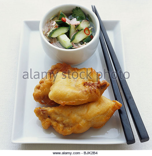 Fried fish in batter with vegetable salad - Stock Image