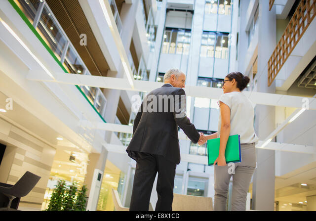 Business people shaking hands in office building - Stock Image