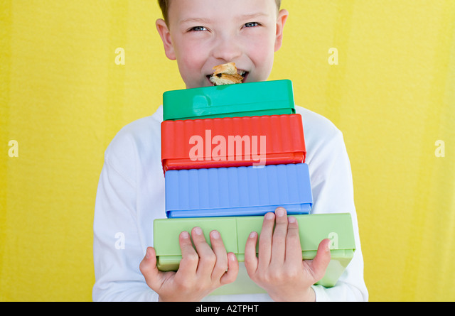 Boy eating snack on top of lunch boxes - Stock Image