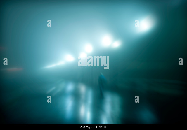 Mysterious figure walking on a wet foggy night. - Stock Image