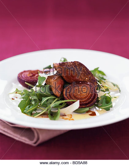 Fried beef fillet with red onions, rocket and Parmesan - Stock Image