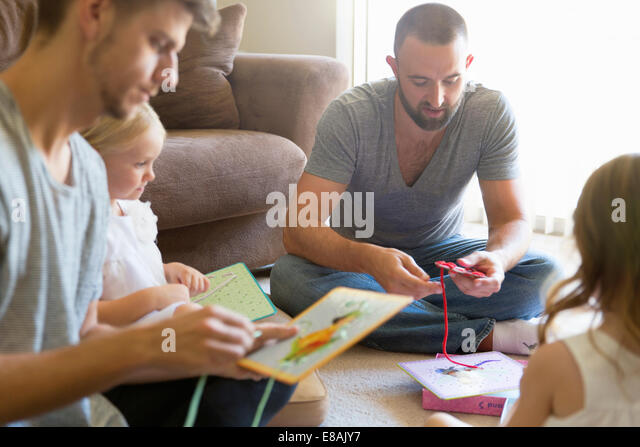Male couple and two daughters threading picture books on sitting room floor - Stock Image