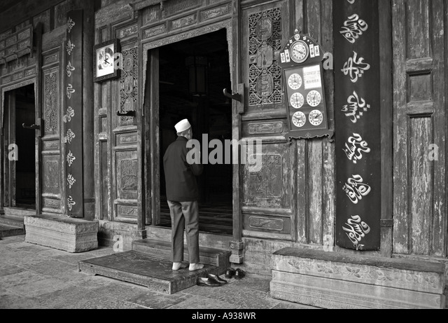 CHINA XI AN Devout Chinese Muslim man removing his shoes outside the elaborately carved and painted doorways of - Stock Image