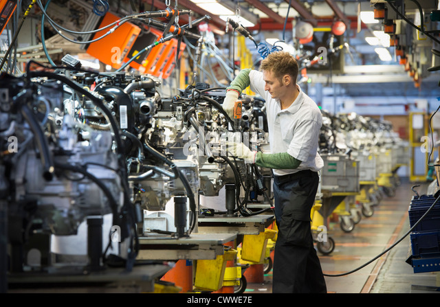 Worker with engines on production line in car factory - Stock Image