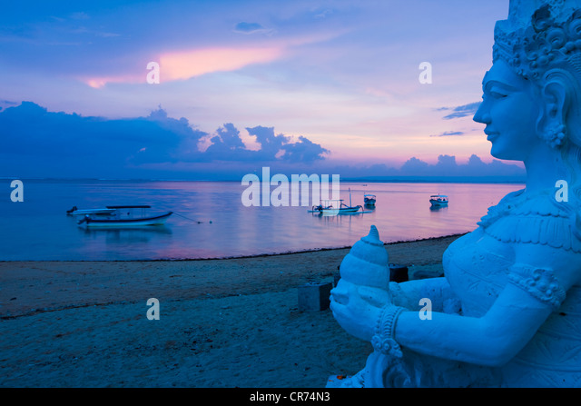 Indonesia, Bali, Sanur, Statue with sea in background at dusk - Stock Image