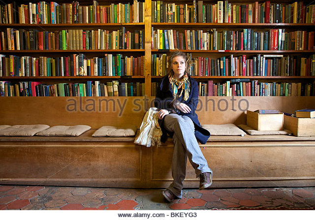 young-woman-sitting-in-a-book-stone-in-f