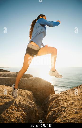 USA, California, San Diego, Woman jogging along sea coast - Stock Image