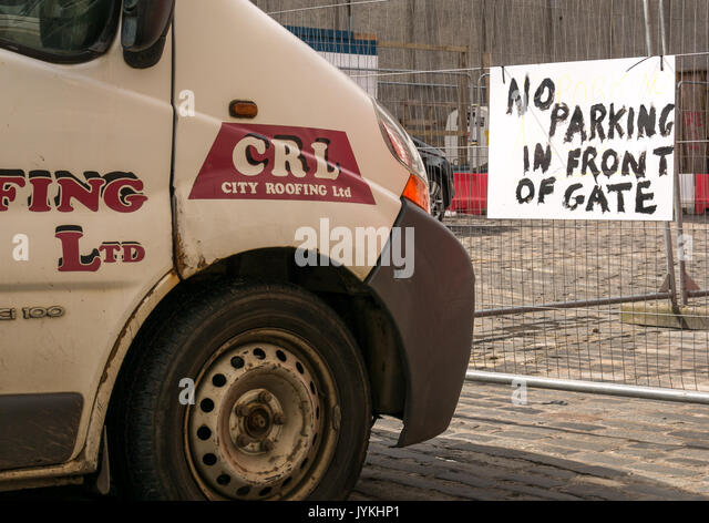 A white workman's van parked directly in front of a hand painted sign saying 'No parking in front of gate' on an Edinburgh Street, Scotland, UK - Stock Image