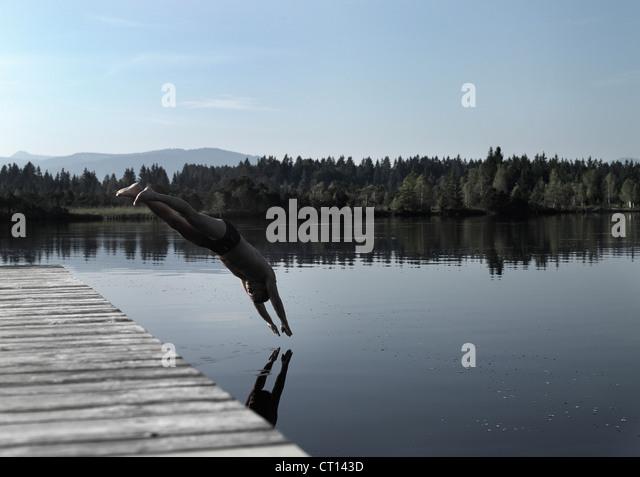 Man diving into still lake - Stock Image