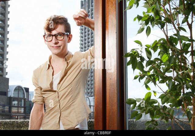 Man smiling on balcony - Stock Image
