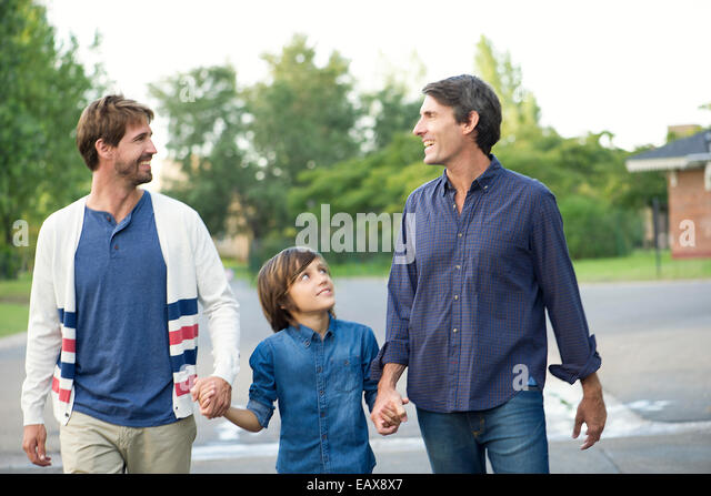 Fathers holding hands with son outdoors - Stock Image