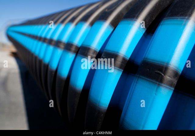 Blue and black stripes on grooved water pipe surface - Stock Image